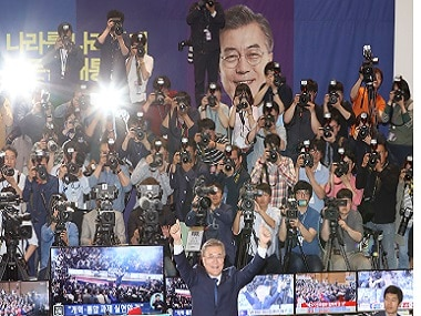 South Korea's presidential candidate Moon Jae-in of the Democratic Party raises his hands in front of the media as his party leaders watch on television the local media's results of exit polls.