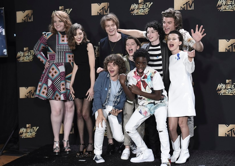 "Shannon Purser, from background left, Natalia Dyer, Charlie Heaton, Noah Schnapp, Finn Wolfhard, Joe Keery, Millie Bobby Brown and from foreground left, Gaten Matarazzo and Caleb McLaughlin, winners of the award for show of the year for ""Stranger Things"" pose in the press room at the MTV Movie and TV Awards at the Shrine Auditorium on Sunday, May 7, 2017, in Los Angeles. (Photo by Richard Shotwell/Invision/AP)"