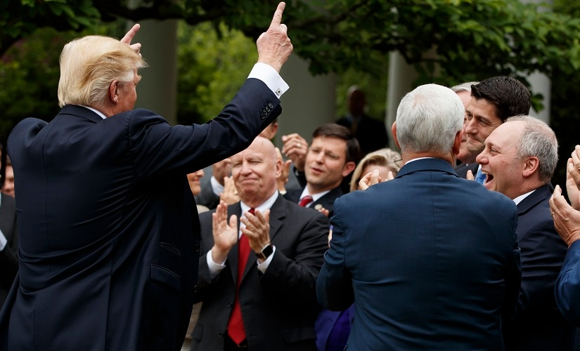 President Donald Trump pumps his hands to GOP House members after the House pushed through a health care bill. AP