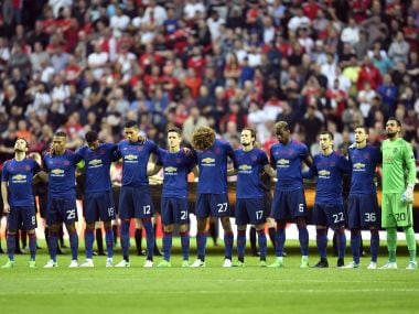 Manchester United players hold a minute's silence as a tribute to the victims of the Manchester bomb attack. AP