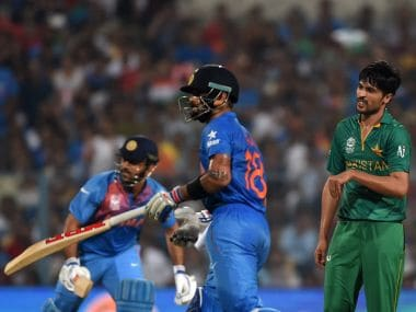 MS Dhoni (L) and Virat Kohli (C) run between the wickets as Pakistan's Mohammad Amir looks on during the World T20. AFP