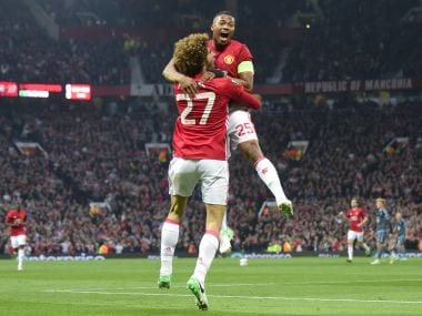 Belgian midfielder Marouane Fellaini (L) celebrates with Manchester United's Ecuadorian midfielder Antonio Valencia (R) after scoring the opening goal of the UEFA Europa League semi-final, second-leg football match between Manchester United and Celta Vigo at Old Trafford stadium in Manchester, north-west England, on May 11, 2017. / AFP PHOTO / Miguel RIOPA