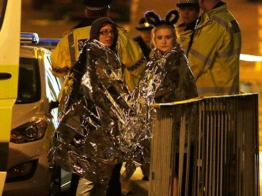 Two women wrapped in thermal blankets stand near the Manchester Arena, where U.S. singer Ariana Grande had been performing, in Manchester. Reuters