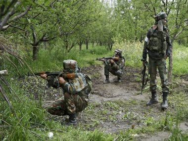 Indian Army personnel taking positions in an orchard field during a crackdown at a village in Shopian district in South Kashmir on Thursday. PTI