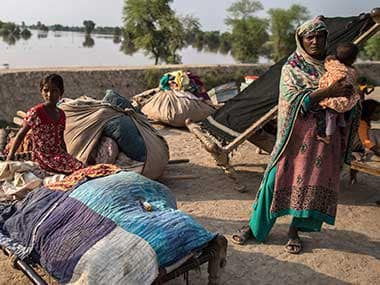 Victims of internal displacement seen beside their belongings in front of a flooded field in Punjab. Reuters