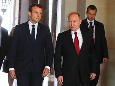 French president Emmanuel Macron (L) and his Russian counterpart Vladimir Putin (R) walk, as they meet for talks in Versailles, near Paris. AP