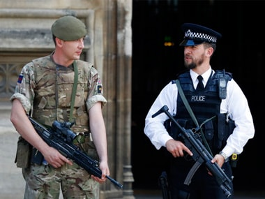 An armed soldier and policeman stand guard at the parliament in London on Thursday. AP