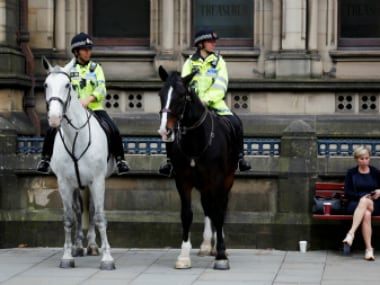 Mounted police officers wait outside the townhall in Manchester. Reuters