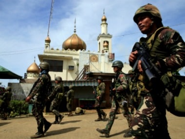 Government troops walk past a mosque before their assault with insurgents , who have taken over large parts of Marawi City, southern Philippines. Reuters