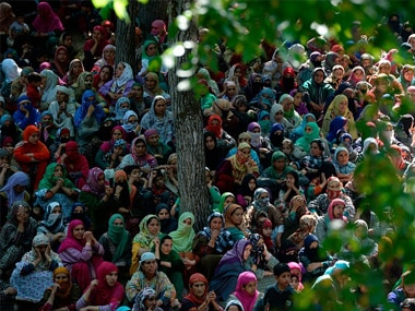 Kashmiri villagers watch the funeral procession of Hizbul commander Sabzar Bhat in Rathsuna Tral, near Srinagar. Getty Images