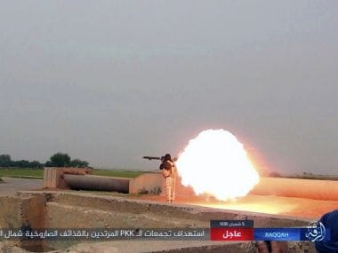 A file photo purports to show an Islamic State fighter firing his weapon during clashes with US-backed Kurdish-led Syrian Democratic Forces, in the northern Syrian province of Raqqa. AP