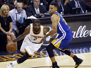Cleveland Cavaliers guard Kyrie Irving (L) dribbles past Golden State Warriors guard Stephen Curry (R) during Game 6 of the NBA Finals in Cleveland, Ohio on June 16, 2016. / AFP PHOTO / Jay LaPrete
