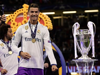 Real Madrid's Portuguese striker Cristiano Ronaldo celebrates next to the trophy after Real Madrid won the UEFA Champions League final football match between Juventus and Real Madrid at The Principality Stadium in Cardiff, south Wales, on June 3, 2017. / AFP PHOTO / JAVIER SORIANO