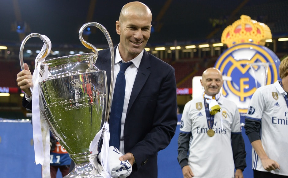 Real Madrid's French coach Zinedine Zidane lifts the trophy after Real Madrid won the UEFA Champions League. AFP