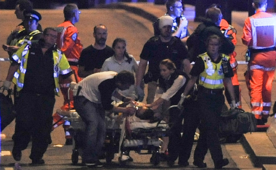 Police and members of the emergency services attend to victims. A total of six civilians are reported to have died in the attack. AFP