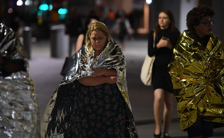 Members of the public, wrapped in emergency blankets leave the scene of the terror attack on London Bridge in central London Saturday. AFP
