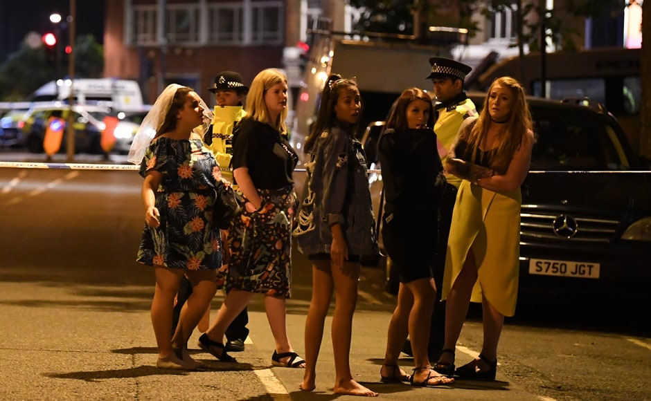 """Women stand at a police cordon set up in London on Sunday morning. Armed police opened fire during what they described as a """"terrorist"""" attack in central London on Saturday after reports of stabbings and a van ploughing into pedestrians just days ahead of a general election. AFP"""