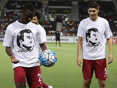 Qatar's national team players Karim Boudiaf (R) and Ali Almoez wear t-shirts bearing portraits of Emir Sheikh Tamim bin Hamad Al-Thani, in support the Qatari leader as they warm up prior to their World Cup 2018 Asia qualifying football match between Qatar and South Korea. AFP