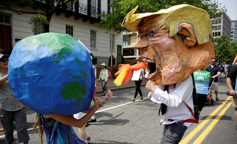 Protesters dressed as the earth and US President Donald Trump pretend to fight. Reuters