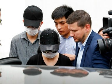 Crown Resorts employees wearing face masks are escorted by securities as they leave the Baoshan District People's Court. AP