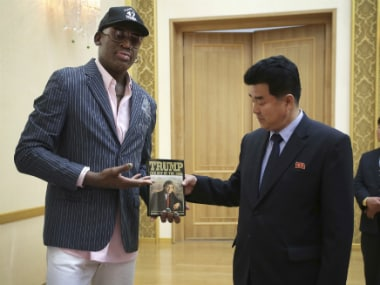"""Former NBA basketball star Dennis Rodman presents a book titled """"Trump The Art of the Deal"""" to North Korea's Sports Minister Kim Il Guk. AP"""