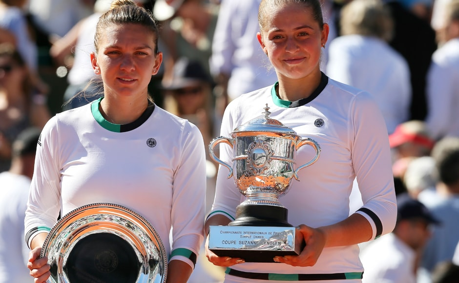 Latvia's Jelena Ostapenko, right, and Romania's Simona Halep hold their trophy after their final match of the French Open at the Roland Garros stadium in Paris. Ostapenko won 4-6, 6-4, 6-3.AP