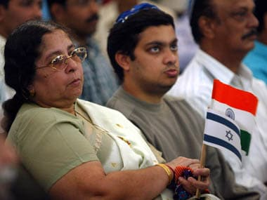 Members of the Indian Jewish community hold Indian and Israeli flags as they listen to Israeli Foreign Minister, Silvan Shalom speak at Magen David Synagogue in Bombay, February 9, 2004. Shalom is on a five-day visit to India to discuss bilateral and regional matters. Israel is likely to sign a $1.1 billion defence deal with India shortly, an Israeli defence industry executive had earlier said on Sunday. REUTERS/Arko Datta REUTERS AD/FMS