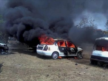 Vehicles in flames after being torched by the agitating farmers at Bhopal-Indore highway in Dewas district on Wednesday. PTI