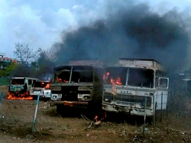 Vehicles in flames after being torched by the agitating farmers in MP. PTI