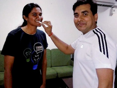 A colleague offers sweets to Nandini K R in Faridabad. PTI