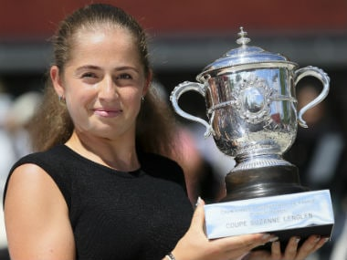 Jelena Ostapenko poses with the trophy during a photo call one day after winning the women's final match of the French Open