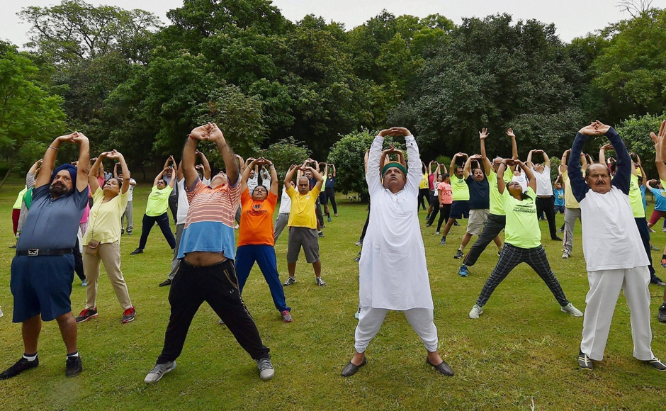 Minister of State for Finance Arjun Ram Meghwal takes part in a mass yoga session at Lodhi Garden ahead of International Yoga Day in New Delhi on Sunday, 18 June 2017. Image courtesy: Kamal Singh, PTI
