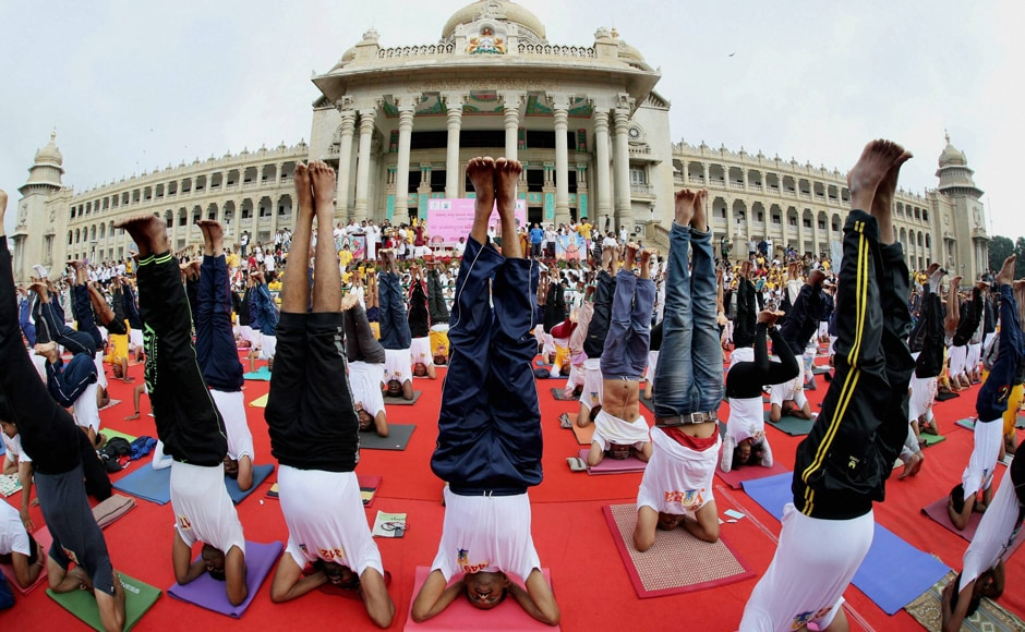 Yoga enthusiasts perform headstands as part of an record attempt, ahead of the International Day of Yoga in front of the Vidhana Soudha, the seat of the State Legislature of Karnataka in Bengaluru on Sunday, 18 June. Image courtesy: PTI
