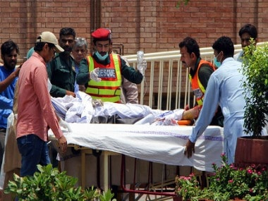 Pakistani rescue worker and hospital staff transport a victim of oil tanker explosion at a hospital in Multan, Pakistan. AP