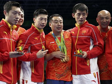 2016 Rio Olympics - Table Tennis - Men's Team - Victory Ceremony - Riocentro - Pavilion 3 - Rio de Janeiro, Brazil - 17/08/2016. Gold medallists Ma Long (CHN) of China, Xu Xin (CHN) of China and Zhang Jike (CHN) of China pose with their coach Liu Guoliang and other members of their team on the podium. REUTERS/Alkis Konstantinidis FOR EDITORIAL USE ONLY. NOT FOR SALE FOR MARKETING OR ADVERTISING CAMPAIGNS. - RTX2MG2C