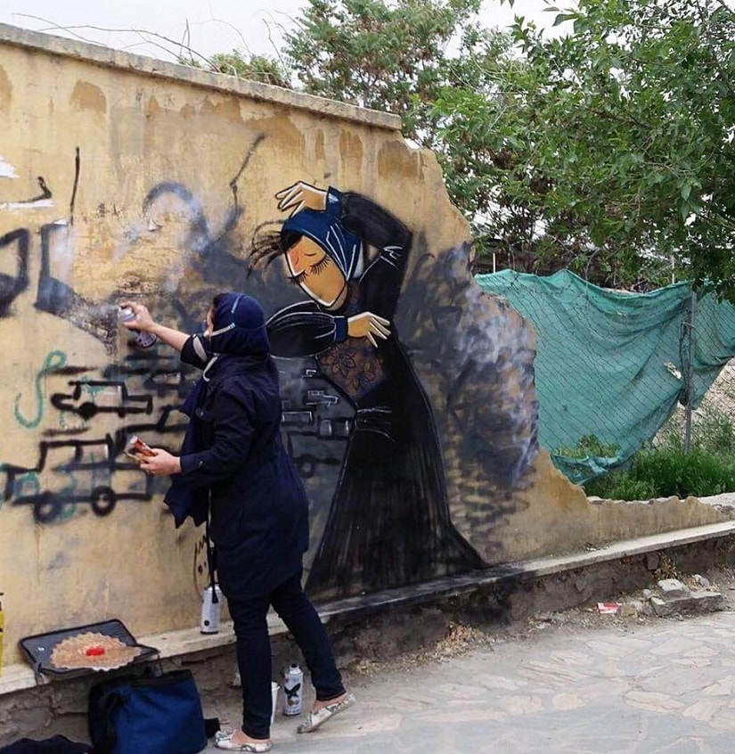Shamsia works on a wall in Kabul. Image via Facebook