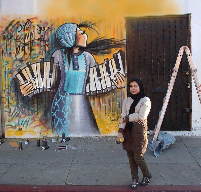 Shamsia stands in front of her artwork. Image via Facebook