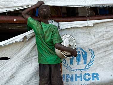 A South Sudanese refugee boy looks through a rip in the tent that serves food in Bidi Bidi refugee settlement, Uganda. AP