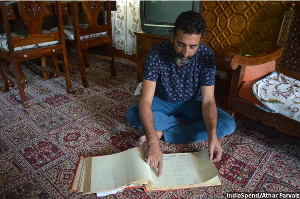 Tariq Ahmad Patloo showing the entries of foreign guests during 1980s from an old log book of his house-boat New Sea Palace.