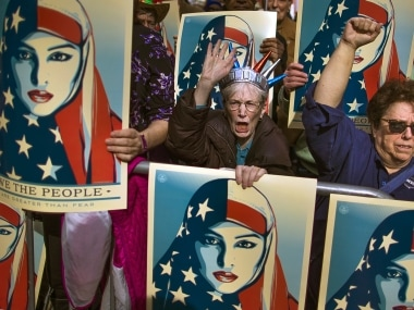 Protestors carry posters at a rally against the travel ban. AP