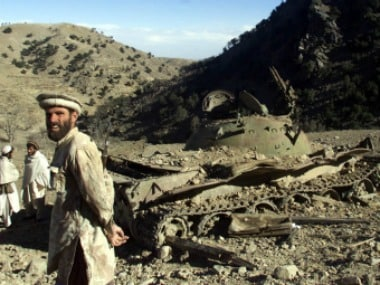 Anti-Taliban Afghan fighters stand beside a destroyed tank in Tora Bora, Afghanistan. Reuters