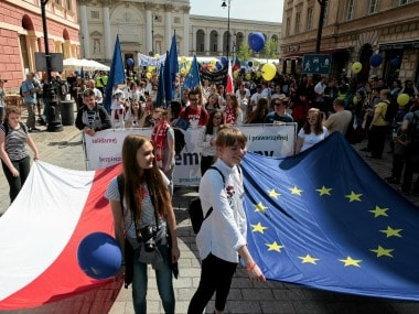 People hold European Union and Polish flags during the annual EU parade in Warsaw, Poland May 6, 2017. Reuters