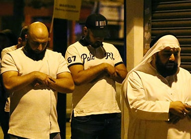 Men pray after the attack. Reuters