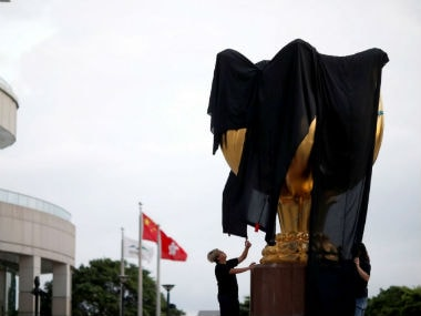 Joshua Wong covering Hong Kong's national symbol with black cloth as a mark of protest. Reuters