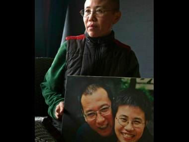 In this Dec. 6, 2012 file photo, Liu Xia, wife of 2010 Nobel Peace Prize winner Liu Xiaobo, poses with a photo of her and her husband. AP