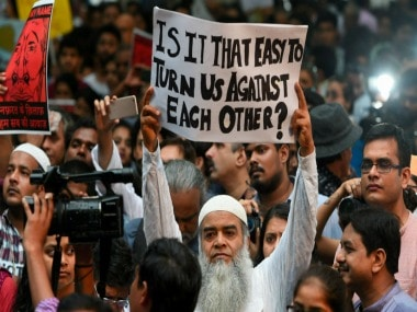 Citizens hold placards during a silent protest. PTI