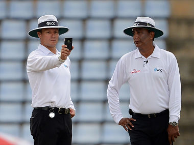 Umpire Richard Kettleborough (L) and checks a light metre as umpire Sundaram Ravi looks on after bad light stopped play on the third day of the opening Test match between Sri Lanka and Australia at the Pallekele International Cricket Stadium in Pallekele on July 28, 2016. / AFP PHOTO / LAKRUWAN WANNIARACHCHI