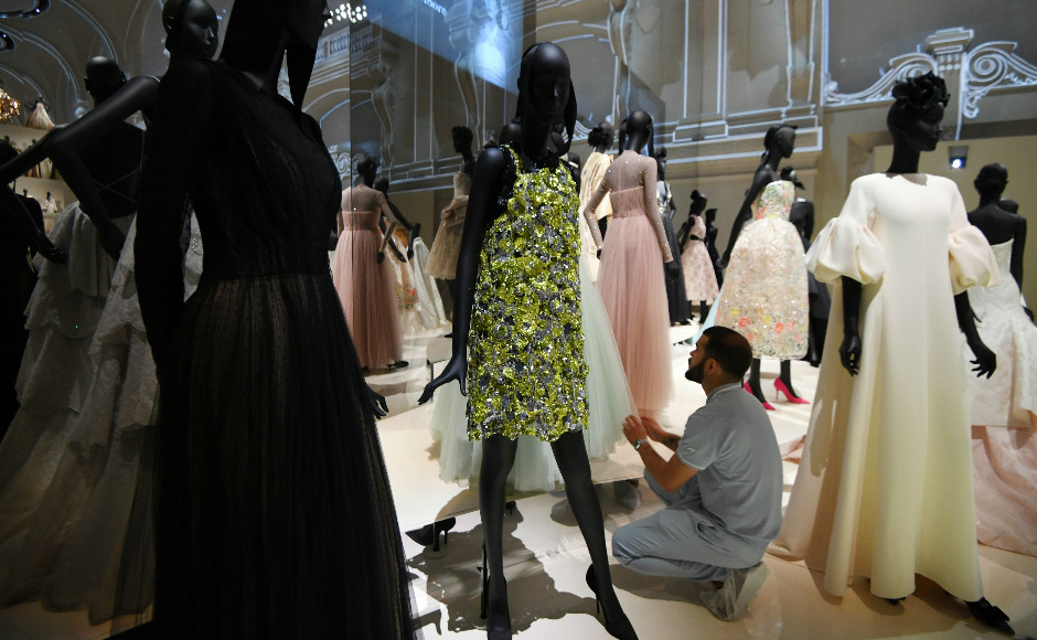 A man adjusts dresses prior to the opening of the Dior exhibition that celebrates the seventieth anniversary of the Christian Dior fashion house. Photo: AFP