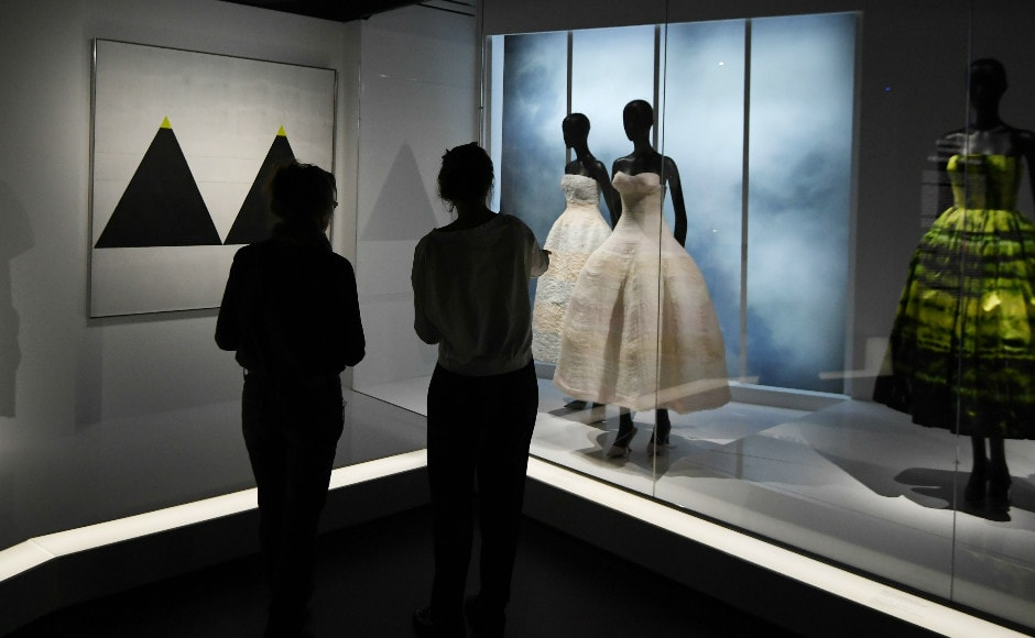 Visitors view dresses during the Dior exhibition. Photo: AFP