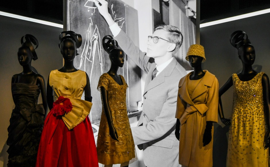 Dresses by French fashion designer Yves Saint Laurent (whose picture is seen behind) are photographed during the Dior exhibition that celebrates the seventieth anniversary of the Christian Dior fashion house on 3 July 2017 in Paris. Photo: AFP